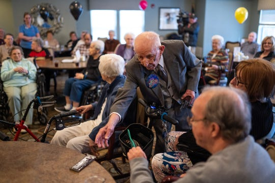 Holocaust survivor Wolf Gruca hands out candy bars to all of the residents and staff at American House Troy on Thursday, Feb. 6, 2020, while celebrating his 100th birthday.