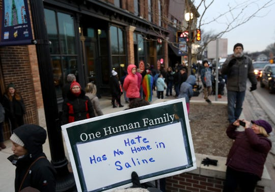 People marched with a variety of signs against racism and bigotry during a rally up and down on Michigan Avenue in downtown Saline, Michigan on Wednesday, February 5, 2020.