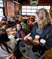 Skylar Ehlert, 28 of Hazel Park listens while serving a variety of beers to a big party inside Founders Brewing Co. on Thursday, February 6, 2020.The taproom reopened at 11 am after being closed for more than 3 months because of a racial discrimination lawsuit.
