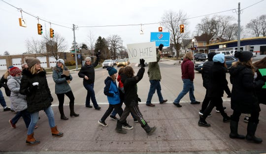 People cross Michigan Avenue during a rally up and down on Michigan Avenue in downtown Saline, Michigan on Wednesday, February 5, 2020.