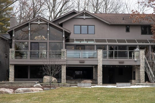 The rear view of the house, facing Deer Lake, shows the lower level walk-out and its stone patio, as well as the raised terraces off the main floor. Photographed in Independence Township, Tuesday, Feb. 4, 2020.