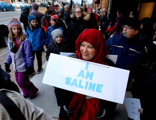 """Valerie Casarez Helmer of Saline with her """"I Am Saline"""" on one side and """"Get Use to It"""" spelled out on the sign other back.Over 250 people came to march against racism and bigotry during a rally up and down on Michigan Avenue in downtown Saline, Michigan on Wednesday, February 5, 2020.The city and the school made national news on Monday when at a parent meeting on diversity and inclusion, racist language was used from one parent to another."""