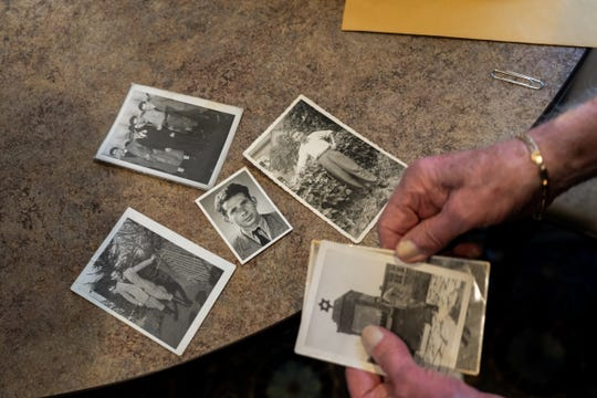Holocaust survivor Wolf Gruca shows old photos of himself during his life that he carried stored in an envelope in his walker at American House Troy on Thursday, Feb. 6, 2020, while celebrating his 100th birthday with family and residents.
