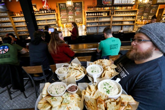 Spencer Girard, 26 of Canton heads out to serve a variety of appetizers to a big party inside Founders Brewing Co. on Thursday, February 6, 2020.The taproom reopened at 11 am after being closed for more than 3 months because of a racial discrimination lawsuit.
