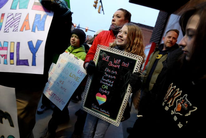 Eliza Farr, 12, and a Saline middle school student, stands with her homemade sign along with her mother Lorissa Farr during a march against racism and bigotry that happened on Michigan Avenue in downtown Saline, Michigan on Wednesday, February 5, 2020. The city and the school made national news on Monday when at a parent meeting on diversity and inclusion, racist language was used from one parent to another.