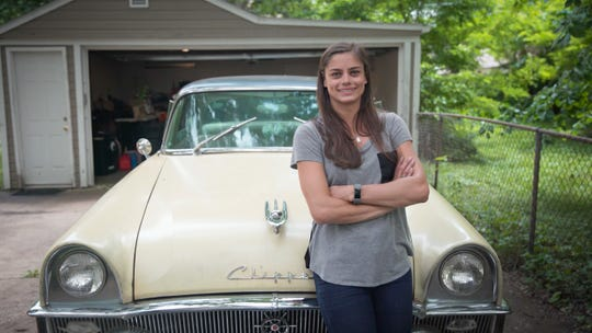 Alex Archer and the 1955 Packard Clipper she is restoring in her home garage.