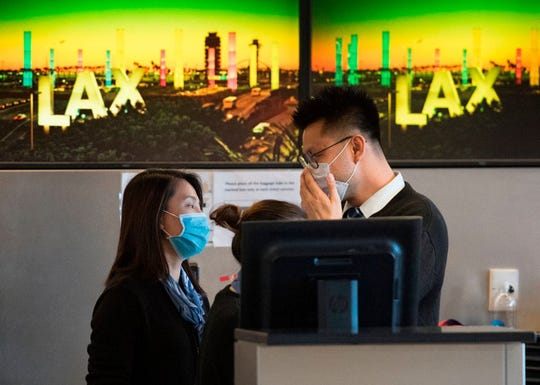 Airline check in staff wear face masks to protect against the spread of the Coronavirus at the Los Angeles International Airport, California, on January 29, 2020.