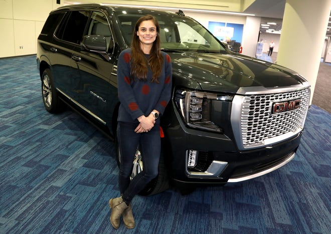 General Motors engineer Alex Archer with the 2021 GMC Yukon with an interior she had a role in designing. Archer worked on the new and innovative power console that can slide back and forth to reveal lots of storage space.