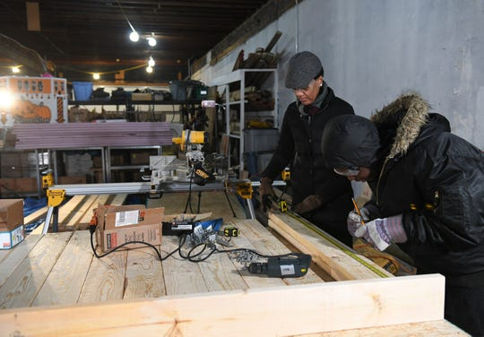 Tool library member Latisha Johnson Davis, left, of Detroit works with Nate Minter, 17, of Detroit to measure and mark beams for The Shop project in January.