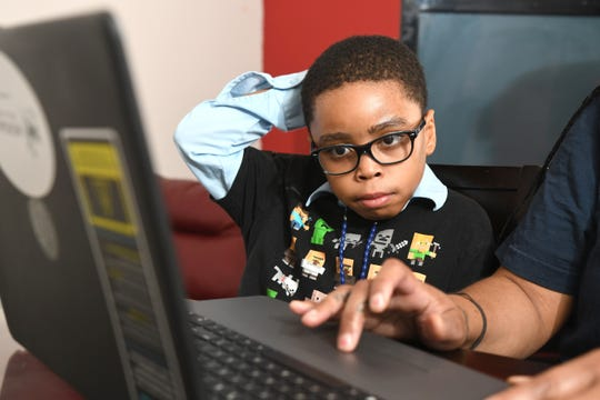 Ryan Cargile, 9, watches his mother Ebony Cargile start his lessons from the Michigan Charter Virtual Academy at their Flint home.