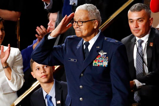 Tuskegee airman Charles McGee, 100, salutes as his great grandson Iain Lanphier looks as President Donald Trump delivers his State of the Union address.