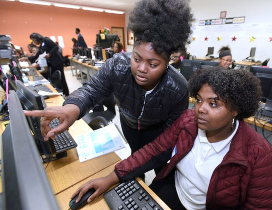 Marianna Eggleston, left, 17, answers a question from classmate Imani Ziyad, 18, both seniors at Martin Luther King High School in Detroit.