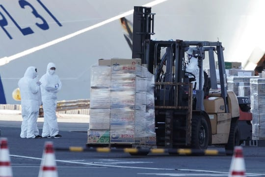 Officials prepare to load supplies to the cruise ship Diamond Princess which is anchored at Yokohama Port in Yokohama, south of Tokyo, Thursday, Feb. 6, 2020.