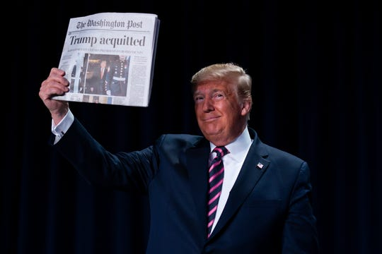 """President Donald Trump holds up a newspaper with the headline that reads """"Trump acquitted"""" during the 68th annual National Prayer Breakfast, at the Washington Hilton, Thursday, Feb. 6, 2020, in Washington."""