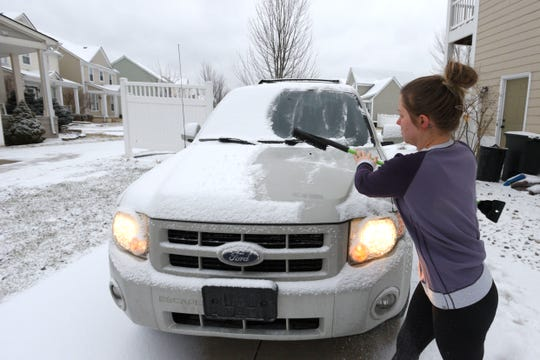 Leah Mutart, 30, of New Haven cleans snow off her SUV before taking her kids to the doctor Thursday morning.