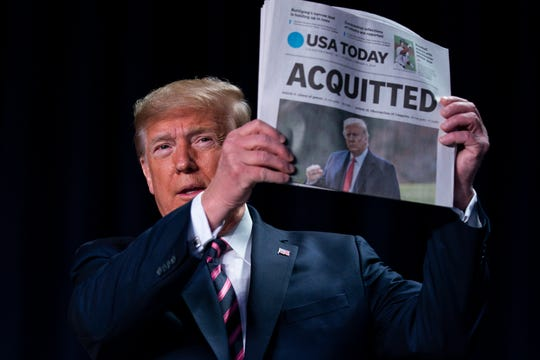"""President Donald Trump holds up a newspaper with the headline that reads """"ACQUITTED"""" at the 68th annual National Prayer Breakfast, at the Washington Hilton, Thursday, Feb. 6, 2020, in Washington."""