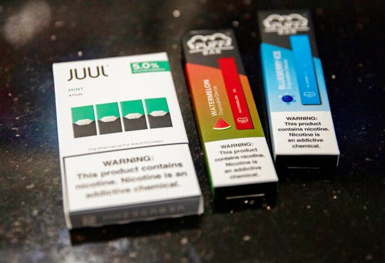 Mint Juul pods next to Puff Bar flavored disposable vape devices at a store in the Brooklyn borough of New York.