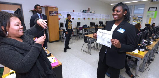 DPSCD spokesperson Chrystal Wilson, left, takes a picture of senior-student Nadia Lawrence, 17, of Detroit, as she poses with her test certificate. She scored a 100% on the test.