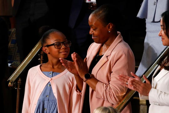 Janiyah, left, and Stephanie Davis of Philadelphia, listens as President Donald Trump delivers his State of the Union address.