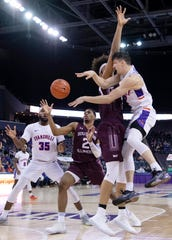 Evansville's Artur Labinowicz (2) dishes off to Evansville's John Hall (35) while being defended by Southern Illinois' Karrington Davis (2) during their game at Ford Center Wednesday night, Feb. 5, 2020.