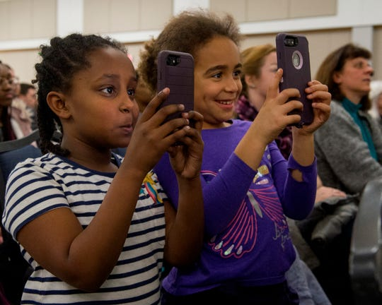 Nahgiste Stein, left, and Chiwala Kaloto, right, take photos of activist Dr. Angela Davis while she delivers her keynote address to community members during the University of Southern Indiana's Mandela Social Justice Day event in Carter Hall Wednesday evening, Feb. 5, 2020.