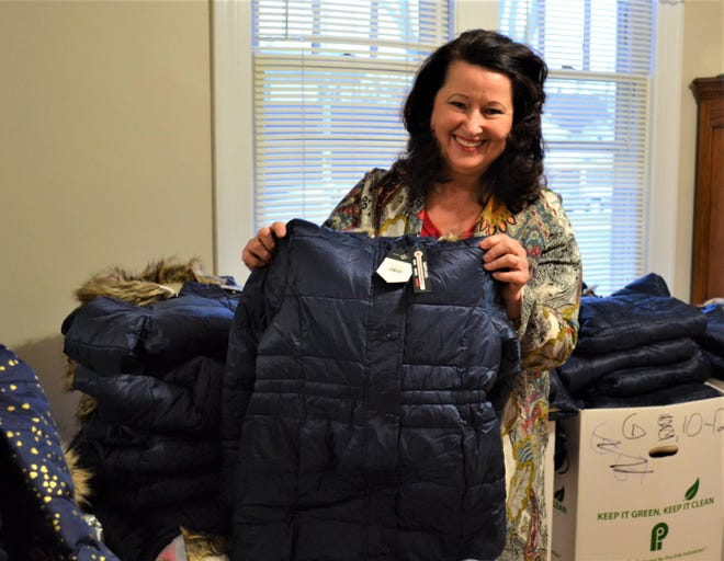 Susan Perry holds one of the thousands of new coats she will give away. Perry's passion for keeping children warm stems from her own difficult childhood.