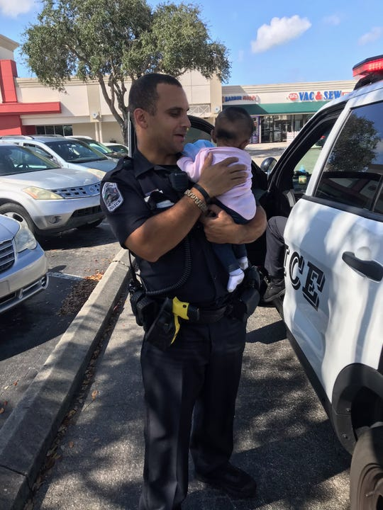A Fort Myers police officer holds a 4-month-old infant left in a locked car by parents while they shopped at Dollar Tree in the Sam's Club Plaza, 5100 S. Cleveland Ave., about 10 a.m. Thursday.