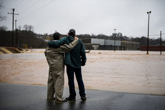 "Barry Crawford puts his arms around Pat Mulkey after they were rescued from the former OWT Plant building in Pickens during a severe rain Thursday, Feb. 6, 2020. ""It's heartbreaking,"" said Mulkey, whose business was going to open in two weeks in the converted building. ""I recently moved the business back to my hometown from Greenville and lost it all. We lost everything."""