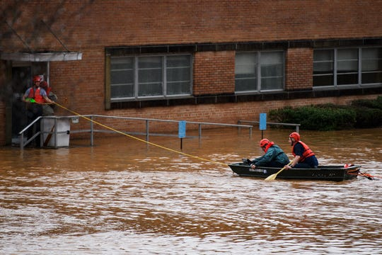 A swift water rescue team gets people to safety as water surrounds the former OWT Plant building in Pickens Thursday, Feb. 6, 2020.