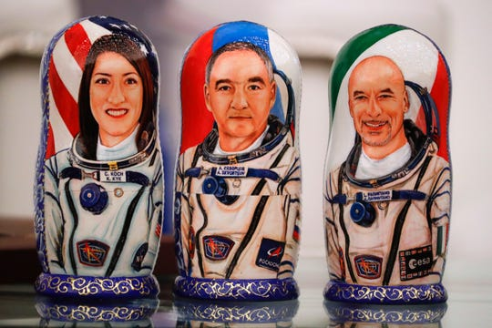 Russian traditional wooden dolls Matryoshka depicting U.S. astronaut Christina Koch, left, Italian astronaut Luca Parmitano, right, and Russian cosmonaut Alexander Skvortsov prior to the astronauts' news conference Thursday after the landing of the Russian Soyuz MS-13 space capsule in the town of Karaganda, Kazakhstan.