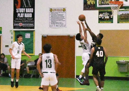 Tiyan High Titans Dewayne Ngirairikl gets a block on JFK's No. 24 Ralf Manalac during their Interscholastic Sports Association Boys Basketball game Feb. 6 at the Islander gym. JFK won 58-49 to improve to 6-1.
