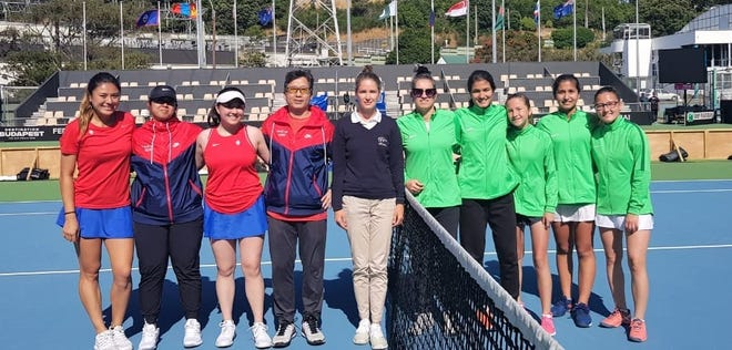 Team Guam, in red and blue, stand with their opponents from Turkmenistan. Team Guam is, from left, Nadine Del Carmen, Charlayne Espinosa, Katie Lai and captain Sam Lai.