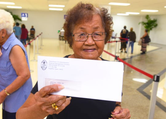 War claimant Rosa Sanchez holds out her war claims check, which she picked up at the Guam War Claims Processing Center in Tamuning Feb. 6. At least 116 more war claims checks will be released Friday.