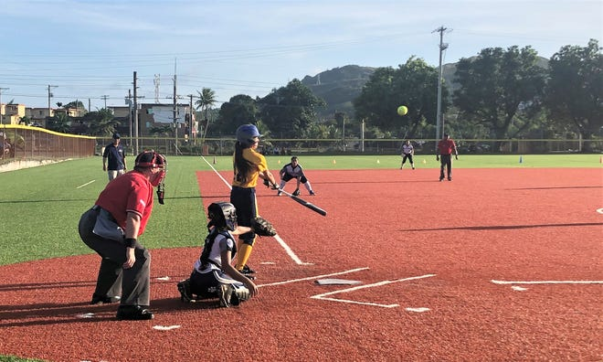 Guam High's Sam WIlliams connects with a pitch but flies out during an Interscholastic Sports Association Girls Softball game Feb. 6 at Guam High against the Academy of Our Lady of Guam. The Cougars won 15-13.