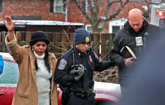 Jamie Gonzalez, from left, IMPD Major Kendale Adams, and FOP President Richard Snyder join police, pastors, and the community during a prayer vigil in the 4100 block of Shady Oak Dr., Thursday, Feb. 6 2020. Four people were fatally shot in an apartment in this Carriage House East, Wednesday night, Feb. 5, 2020.  Gonzalez lives near the apartment complex and came to support the group praying.  She has lived nearby 32 years and never saw anything like this, she said.