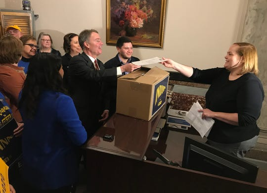 Mayor Joe Hogsett, alongside Pete for America volunteers, hands over more than 8,300 signatures to Angie Nussmeyer, co-director of the Indiana Election Division, to officially place Pete Buttigieg on Indiana's Democratic primary ballot, Thursday, Feb. 6, at the Indiana Statehouse.