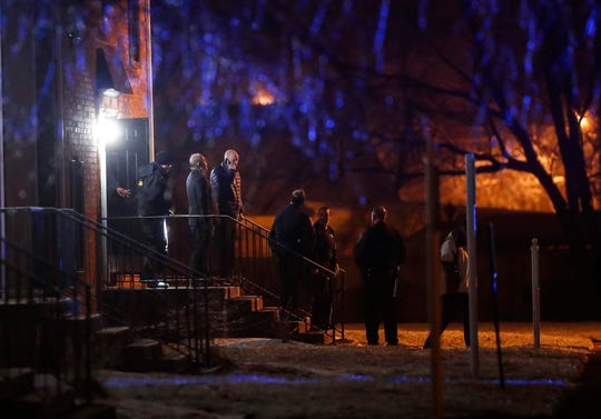 Officers walk out of the apartment complex where four people, one woman and three men, were found dead in the 4100 block of Shady Oak Dr., Indianapolis, Wednesday, Feb. 5, 2020. Indianapolis Metropolitan Police Department responded to a call for gunshots at 10:25 p.m.