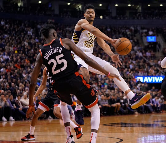 Feb 5, 2020; Toronto, Ontario, CAN; Indiana Pacers guard Jeremy Lamb (26) passes the ball by Toronto Raptors forward Chris Boucher (25) during the first half at Scotiabank Arena.