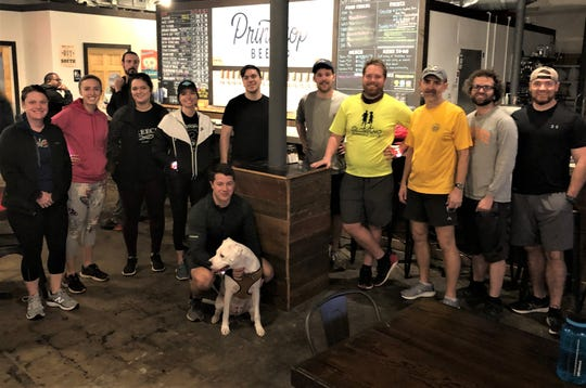 """The Slow Kno Running Club prepares to head out for its Tuesday run on Feb. 4 at Printshop Beer Co. Founders are David Weadon and Scott Crammond, pictured to the left of the column. Some club members show up with a friend or two, while others turn up on their own. """"I would say that about 50% of people come to see what we have going on,"""" said Crammond. """"Another quarter are new to town and are looking to meet more people."""""""
