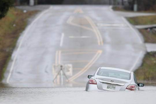 A stranded vehicle is seen submerged in water along Beaver Creek Road in Powell on Thursday.
