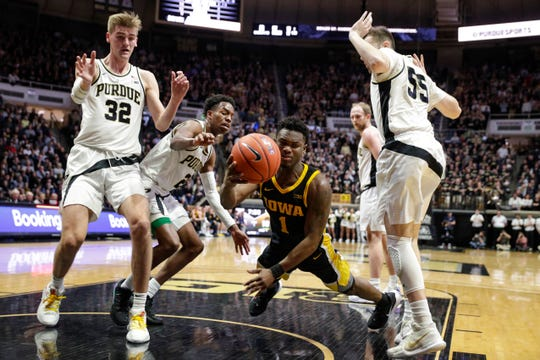 Iowa guard Joe Toussaint (1) falls after being fouled, between Purdue center Matt Haarms (32) and guard Sasha Stefanovic (55) during the first half of an NCAA college basketball game in West Lafayette, Ind., Wednesday, Feb. 5, 2020. (AP Photo/Michael Conroy)