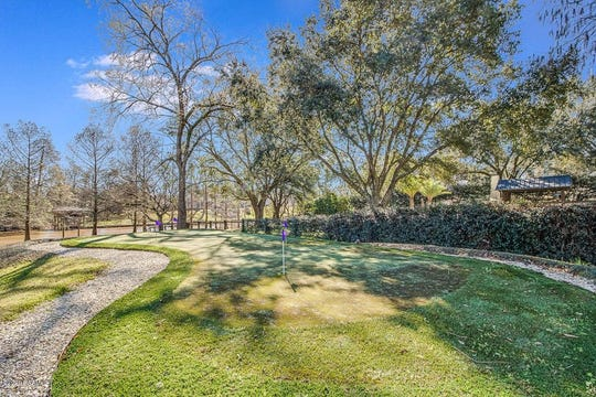 Vermilion River mansion has puttinggreen, floor to ceiling wine rack and custom staircase. Oasis-like backyard has massive covered seating and 900 square foot pool house. Formal and informal living areas lead to the kitchen, which has brick arches with a large wet bar.