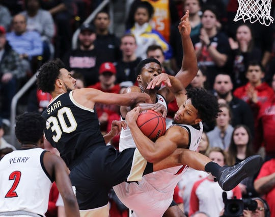 U of L's Dwayne Sutton (24) and Steven Enoch (23) battled Wake Forest's Olivier Sarr (30) for possession during their game at the Yum Center Louisville, Ky. on Feb. 5, 2020.