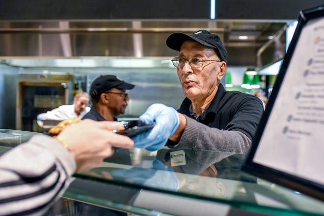 Employee Muhammad Khan serves a customer fried pork that was sourced from the university at the Great Lakes Plate vendor on Thursday, Feb. 6, 2020, at the South Pointe dining hall at Case Hall on the Michigan State University campus in East Lansing.