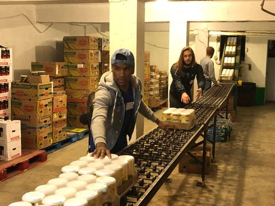 Holy Family College students help sort food at Peter's Pantry in Manitowoc as part of HFC Serves Day Feb. 6.