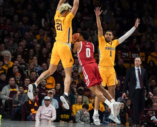 Wisconsin guard D'Mitrik Trice is shut down by Minnesota's Jarvis Omersa (21) as he looks to get off a a shot during the first half.