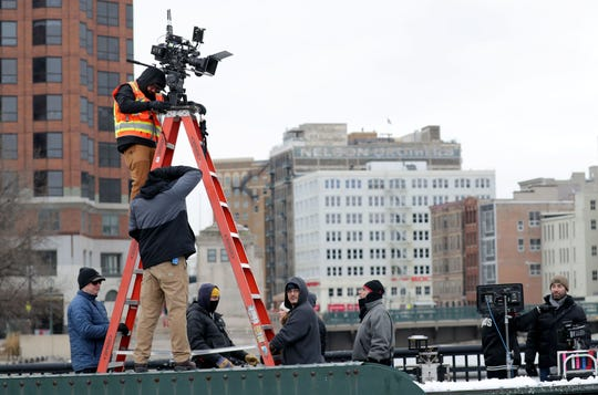Cast and crew members work on filming on a closed State Street bridge in downtown Milwaukee on Thursday.