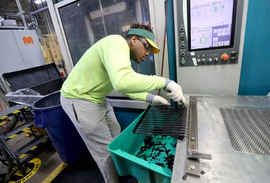 David Jones, a machine operator, produces rubber inner tube parts in the injection molding area at Molded Dimensions.