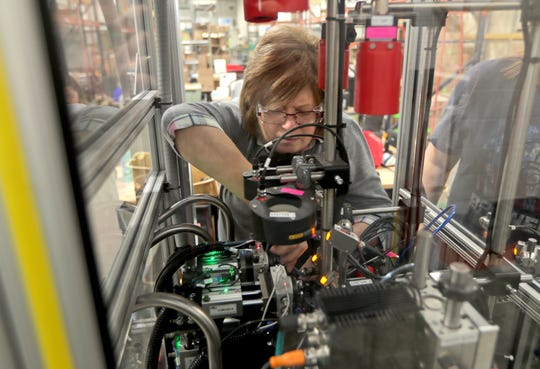 Rhonda Ranz, works on a part inspection machine at Molded Dimensions in Port Washington.
