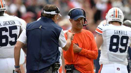 Auburn coach Gus Malzahn (left) bumps fists with defensive coordinator Kevin Steele (right) during a win at Arkansas on Arkansas on Saturday, Oct. 19, 2019 in Fayetteville, AK